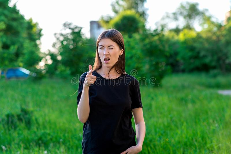 Beautiful brunette girl. Summer in nature among green bushes. In black T-shirt. He shows his hands tin You`re super royalty free stock photos