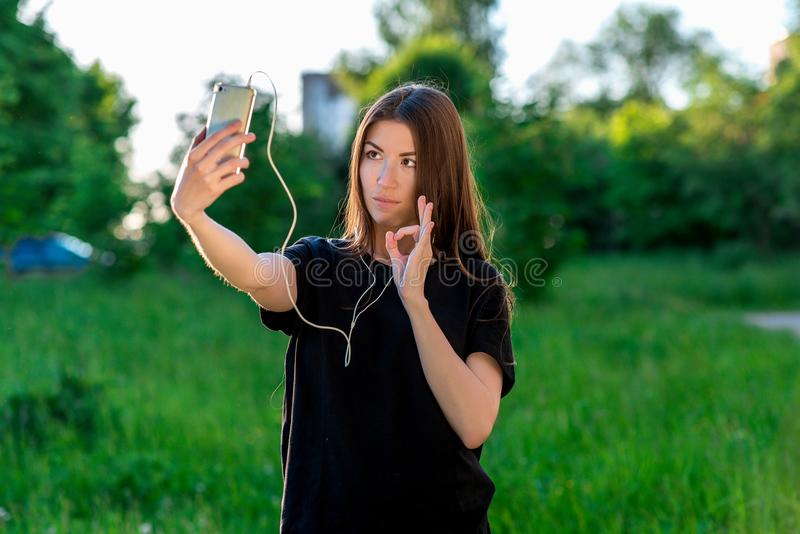 Beautiful brunette girl in the summer at the park calls on the phone with a hand gesture shows OK royalty free stock images