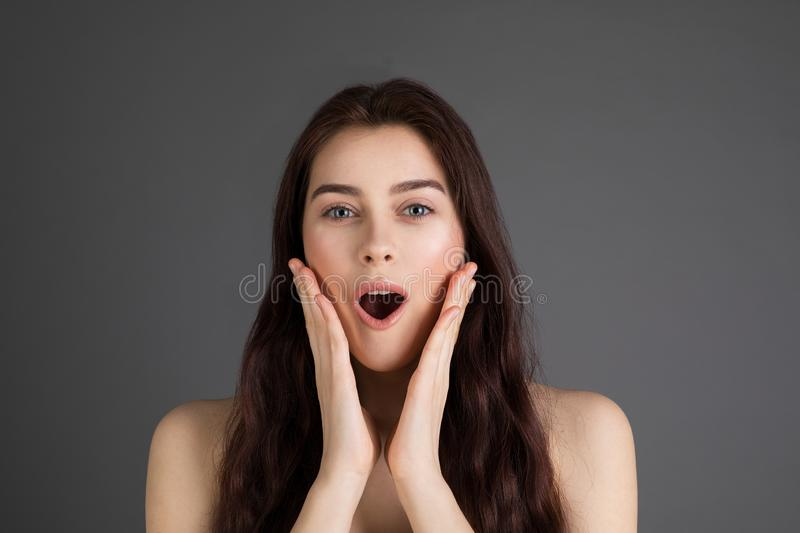 Beautiful brunette girl surprised and put her hands to her face royalty free stock image