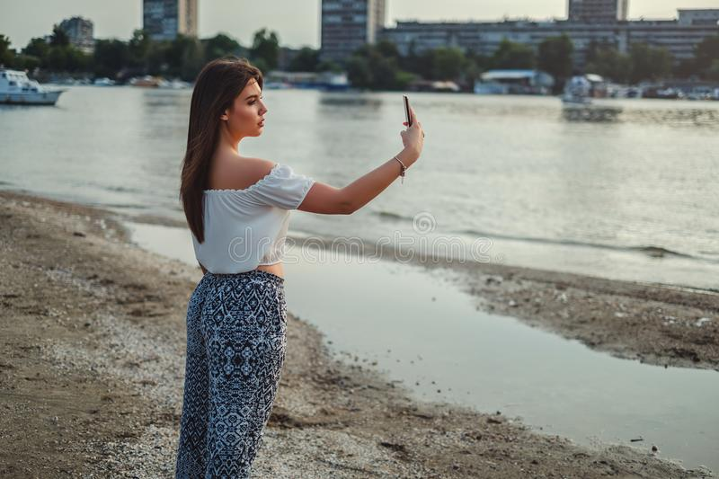 Beautiful girl taking selfie on the beach royalty free stock photography