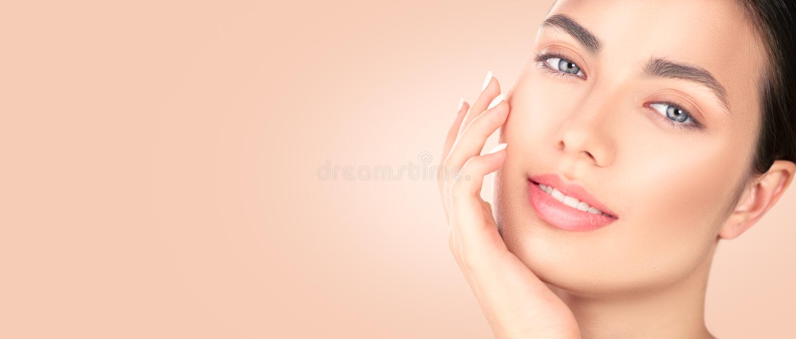 Beautiful brunette girl touching her face. Perfect fresh skin. Spa beauty portrait. Youth and skincare concept stock photo