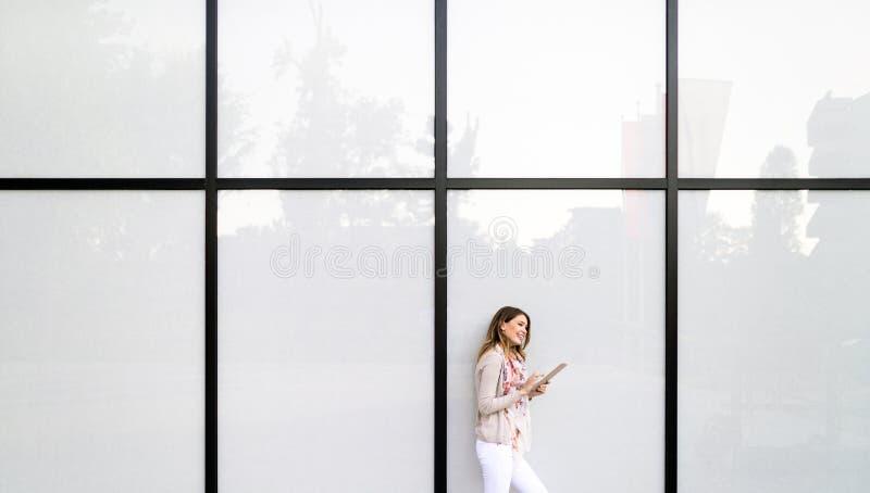 Beautiful brunette girl using smart phone for work, freelance, blogging, studying, shopping. Beautiful brunette woman using mobile for work, freelance, blogging royalty free stock photos