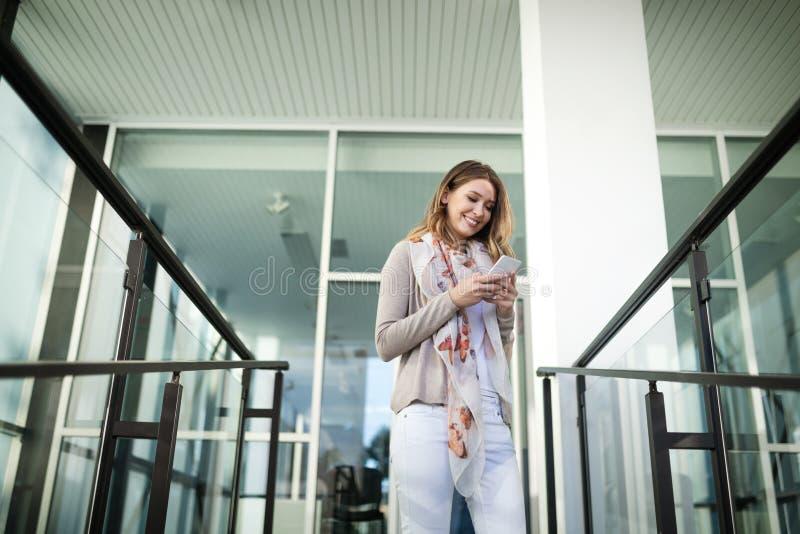 Beautiful brunette girl using smart phone for work, freelance, blogging, studying, shopping. Beautiful brunette woman using mobile for work, freelance, blogging stock image