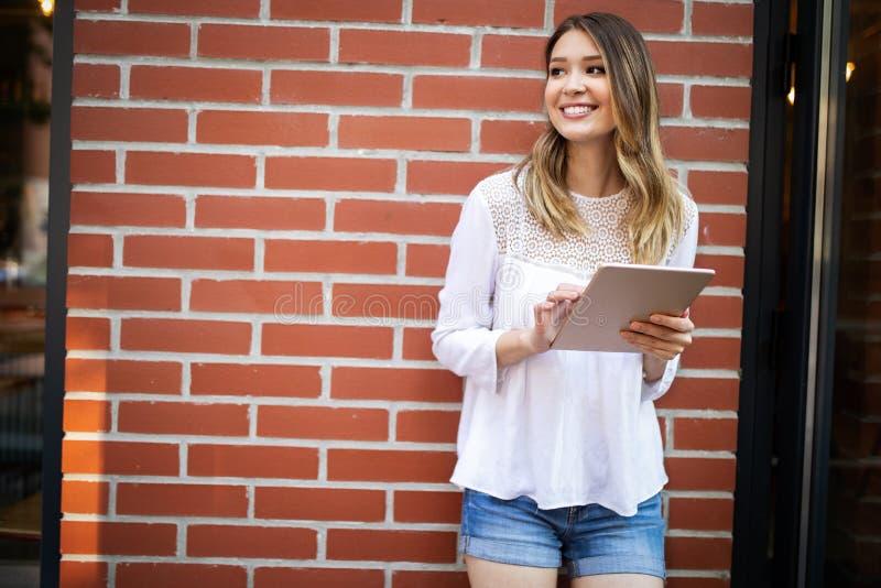 Beautiful brunette girl using tablet for work, freelance, blogging, studying, shopping. Beautiful brunette woman using tablet for work, freelance, blogging stock image