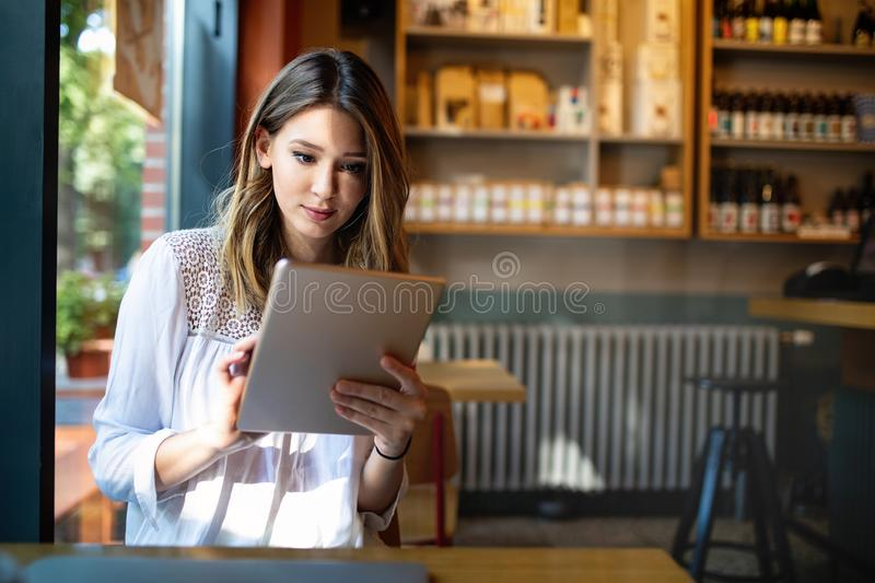 Beautiful brunette girl using tablet for work, freelance, blogging, studying, shopping. Beautiful brunette woman using tablet for work, freelance, blogging royalty free stock image
