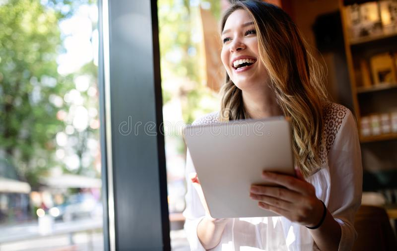 Beautiful brunette girl using tablet for work, freelance, blogging, studying, shopping. Beautiful brunette woman using tablet for work, freelance, blogging stock images