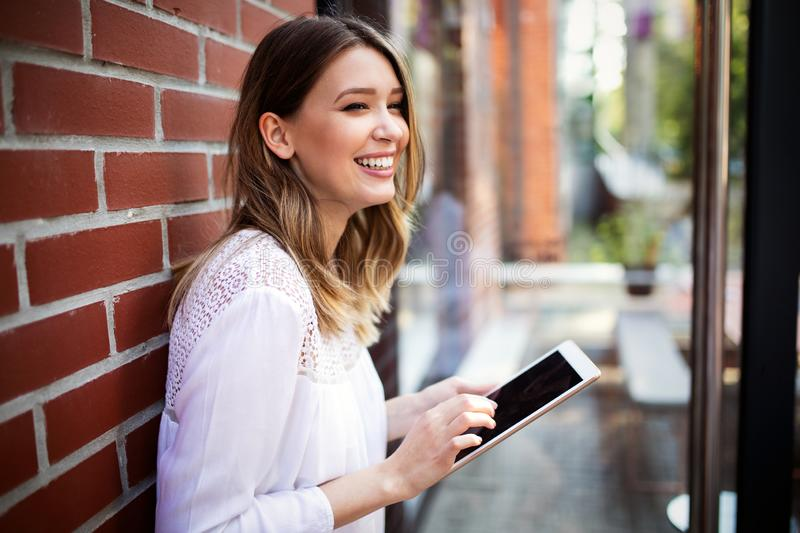 Beautiful brunette girl using tablet for work, freelance, blogging, studying, shopping. Beautiful brunette woman using tablet for work, freelance, blogging stock photos