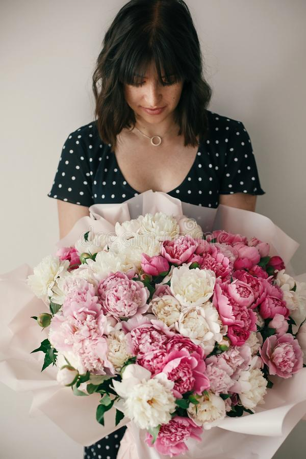 Beautiful brunette girl in vintage dress holding big bouquet with pink and white peonies. Happy stylish woman with peony flowers. In room. International Womens stock images
