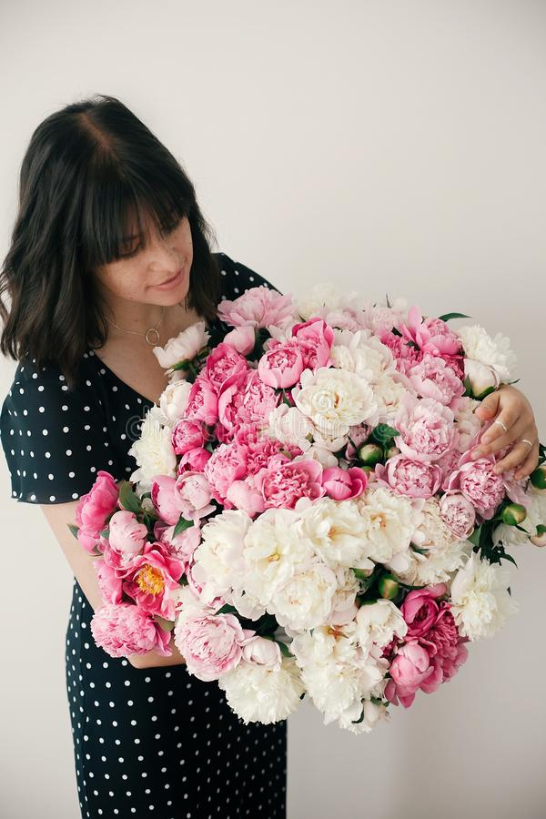 Beautiful brunette girl in vintage dress holding big bouquet with pink and white peonies. Happy stylish woman with peony flowers stock photo