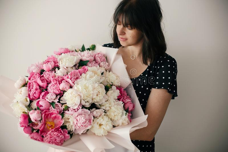 Beautiful brunette girl in vintage dress holding big bouquet with pink and white peonies. Happy stylish woman with peony flowers. In room. International Womens royalty free stock image