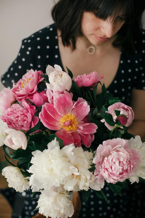 Beautiful brunette girl in vintage dress holding modern bouquet with pink and white peonies. Happy stylish woman with peony stock image