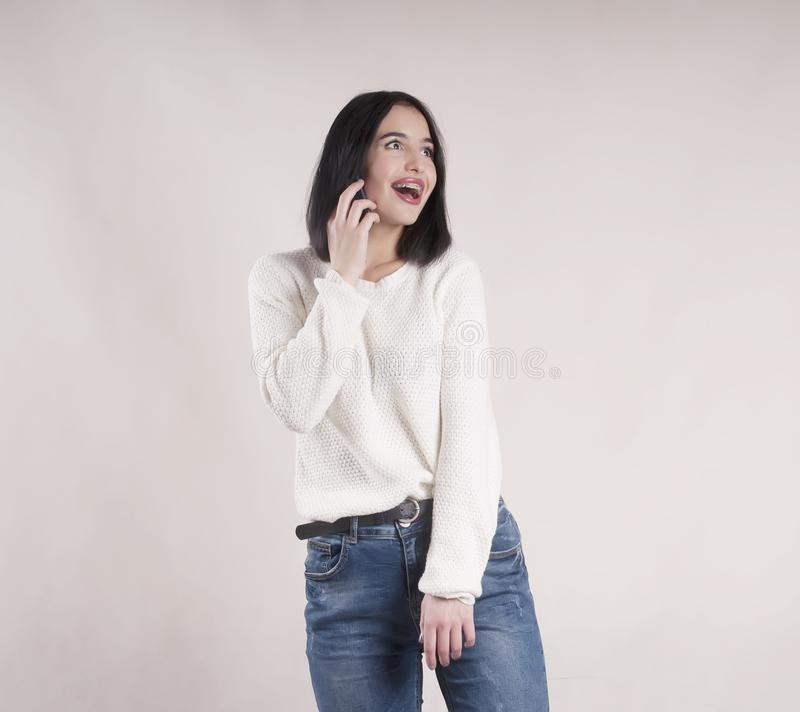 Beautiful brunette girl wearing jeans sweater with phone studio royalty free stock image