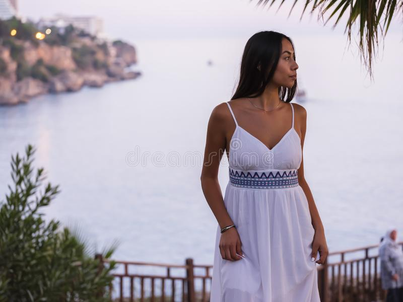 Beautiful brunette girl in a white dress waiting near sea at sunset royalty free stock image