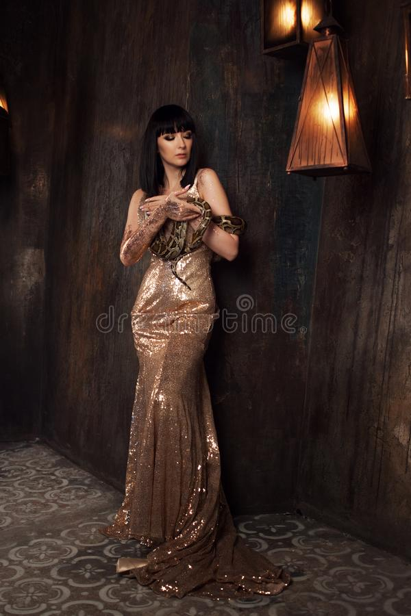 Beautiful and mysterious brunette in a gold dress and with a snake. Beautiful brunette in a gold dress and with a snake royalty free stock image
