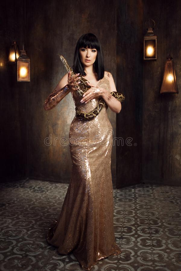 Beautiful and mysterious brunette in a gold dress and with a snake. Beautiful brunette in a gold dress and with a snake royalty free stock photo