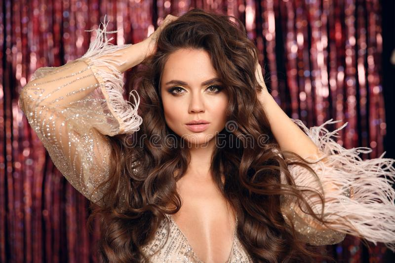 Beautiful brunette with Healthy wavy hair. Beauty Makeup. Fashion Girl in Glamour dress with feather sleeves Isolated on bright. Bokeh Christmas lights stock image