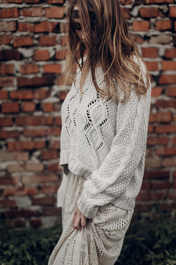 Beautiful brunette hipster woman in white boho sweater and dress stock photos