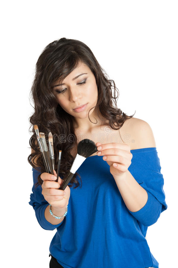 Beautiful brunette holding a makeup brush royalty free stock images