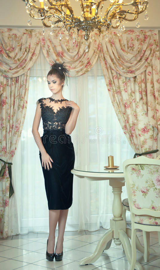 Beautiful brunette lady in elegant black lace dress posing in a vintage scene. Young sensual fashionable woman on high heels stock images