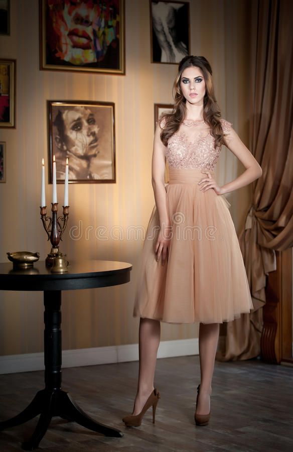Beautiful brunette lady in elegant nude colored dress posing in a vintage scene. Young sensual fashionable woman on high heels with pictures decorated wall as royalty free stock photo