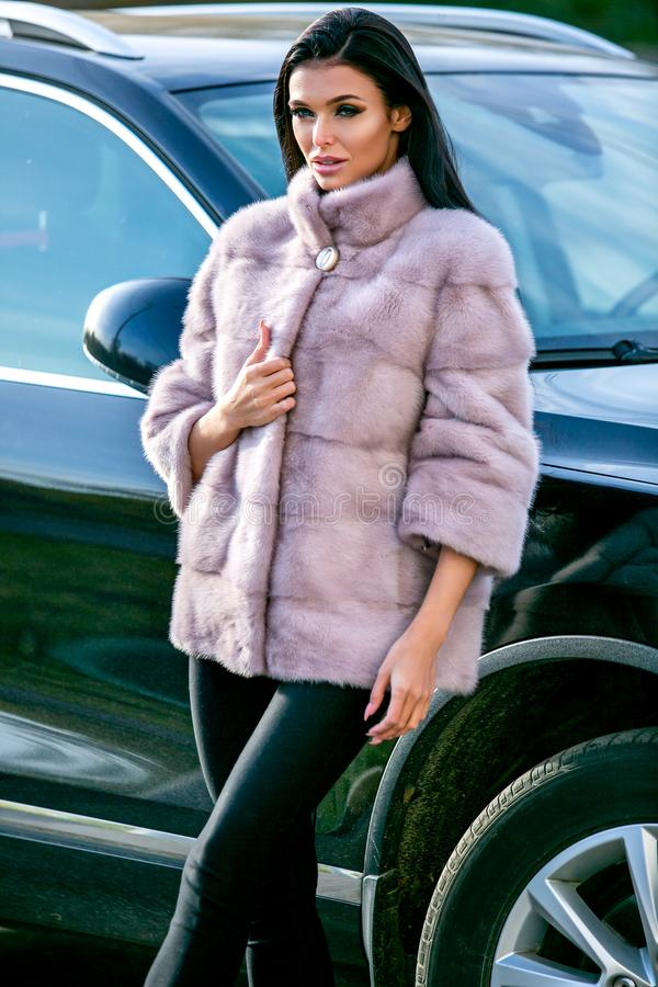 A beautiful brunette in a light-colored fur coat and black trousers is standing near a car on an autumn sunny day, looking sexuall royalty free stock photos