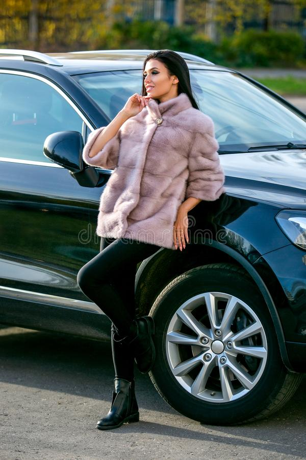 A beautiful brunette in a light fur coat and black trousers is standing near the car on an autumn sunny day and smiling stock photography