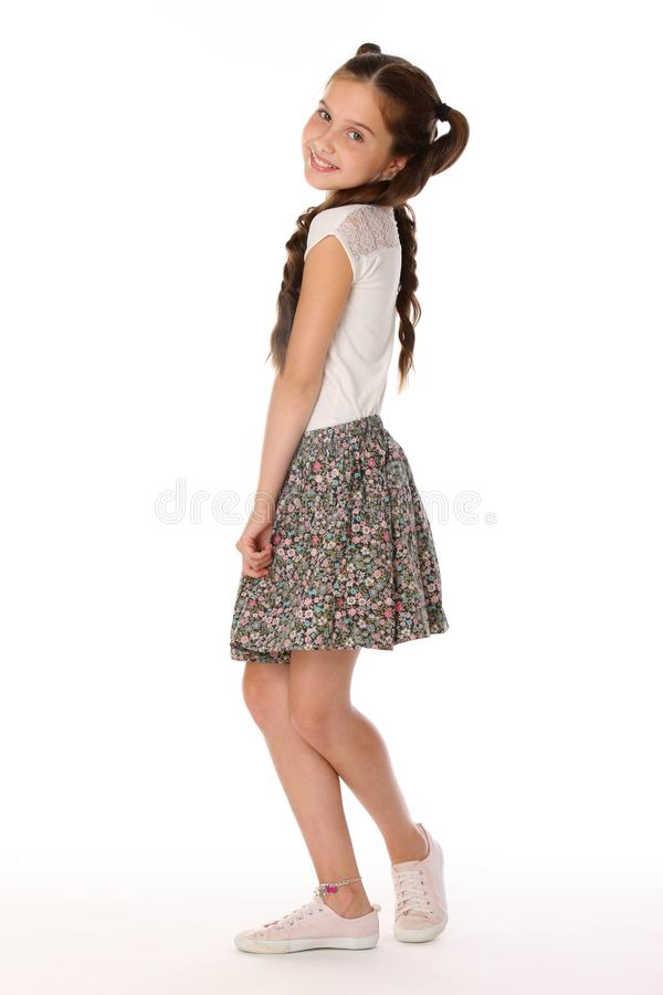 Beautiful brunette little girl 12 years old posing in a skirt with bare legs stock photos