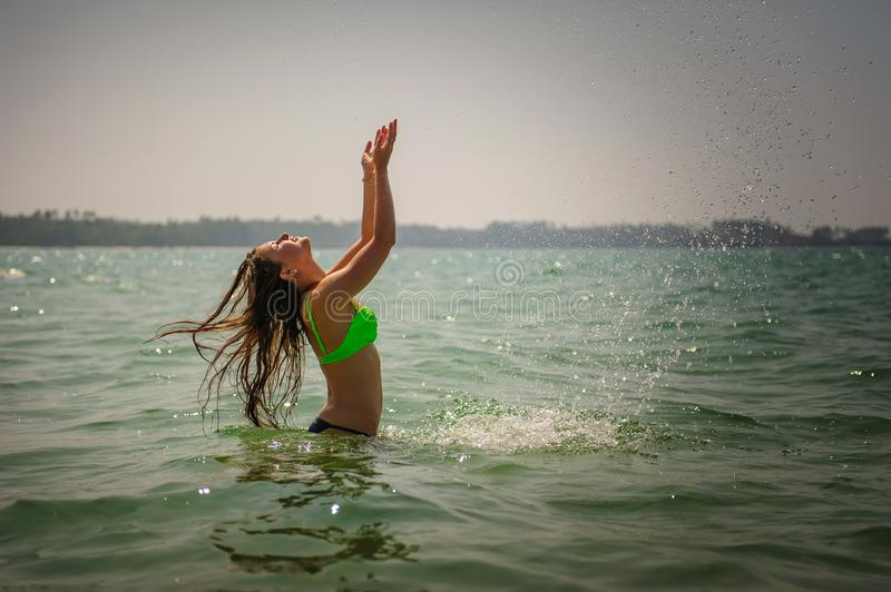 Beautiful brunette with long hair stands waist-deep in the ocean and splashes her hands in water. Young slender girl in bright royalty free stock photo