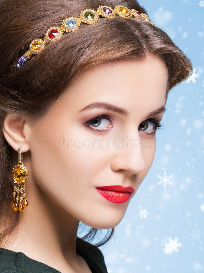 Beautiful brunette with luxury golden necklace over blue winter royalty free stock photos