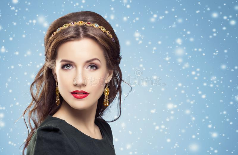 Beautiful brunette with luxury golden necklace over blue winter royalty free stock photography