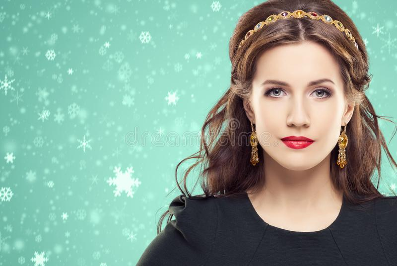 Beautiful brunette with luxury golden necklace over cyan winter stock image