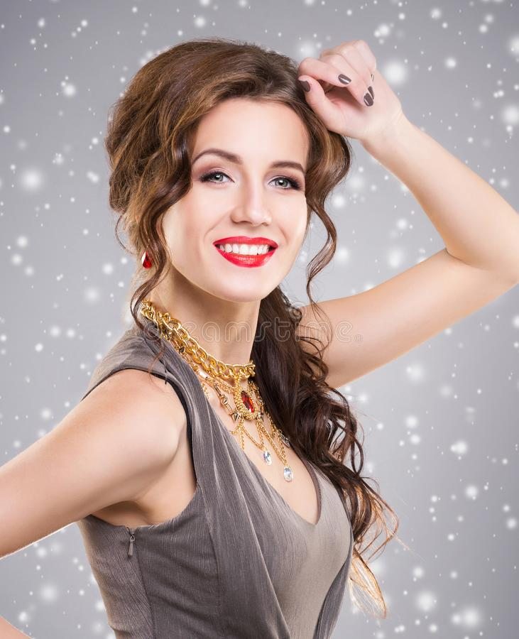 Beautiful brunette with luxury golden necklace over grey winter royalty free stock image