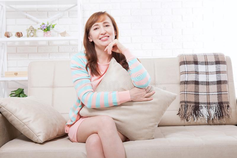 Beautiful brunette middle age woman dreaming at home. Mock up and copy space. Menopause stock photography