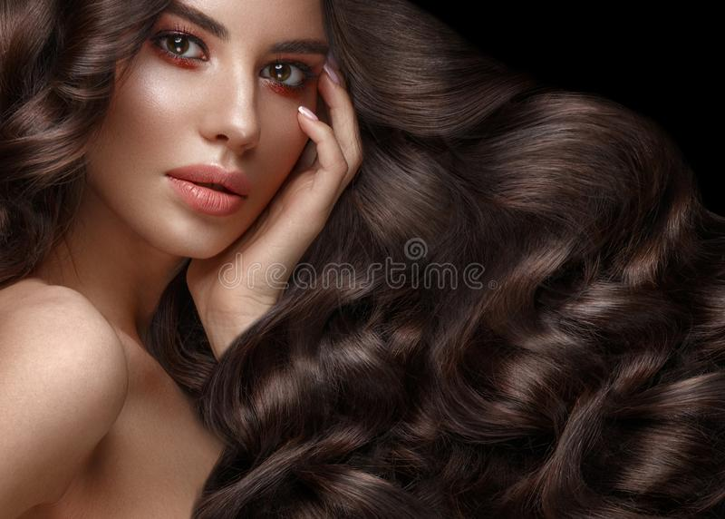 Beautiful brunette model: curls, classic makeup and full lips. The beauty face. Beautiful brunette model with curls, classic makeup and full lips. The beauty of royalty free stock photography