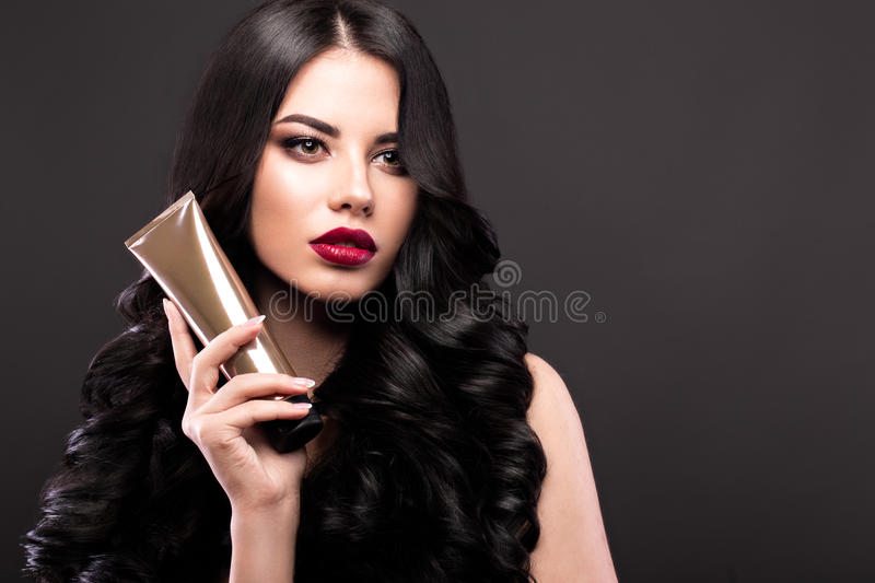 Beautiful brunette model: curls, classic makeup and red lips with a bottle of hair products. The beauty face. royalty free stock photos