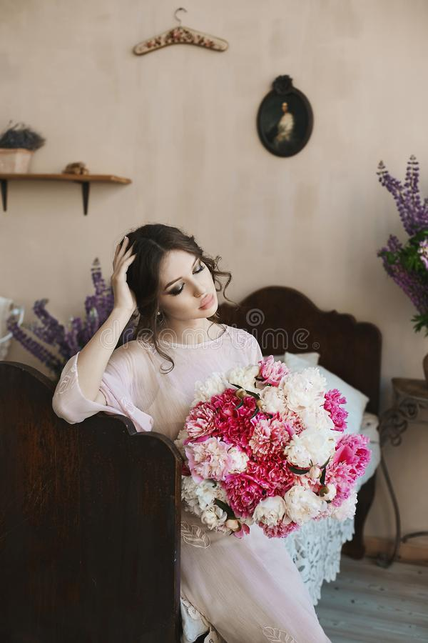 Beautiful brunette model girl with big seductive lips and with blue eyes in fashionable dress with big bouquet of pink stock images