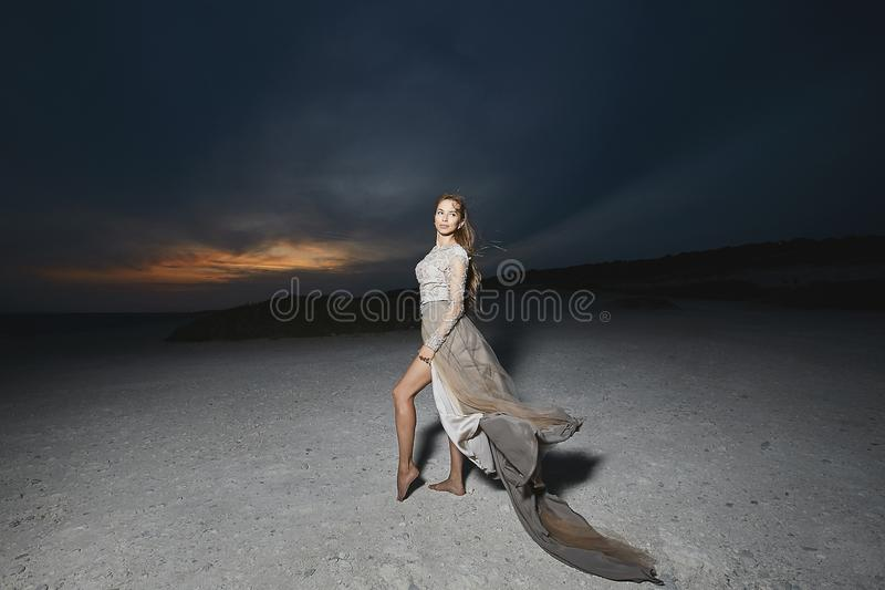 Beautiful brunette model girl with long sexy legs in fashionable lace dress posing at the sea coast at the sunset with stock photography