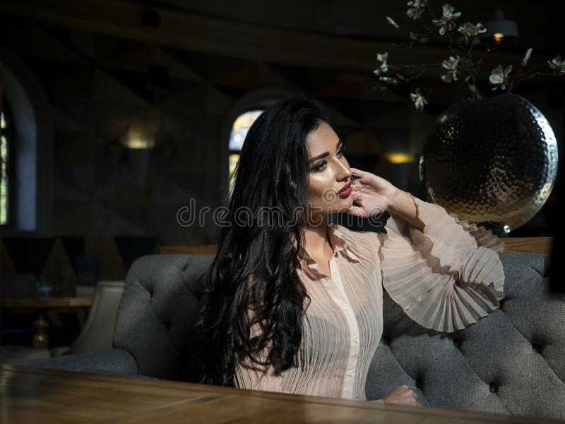 Beautiful brunette model sitting on a table in a restaurant and posing.photo model on photo session stock images