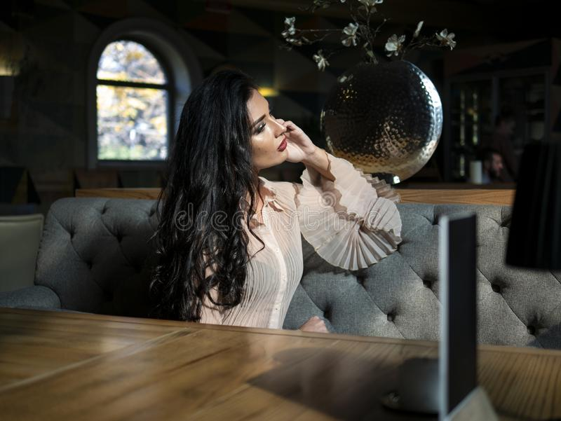 Beautiful brunette model sitting on a table in a restaurant and posing.photo model on photo session stock photography