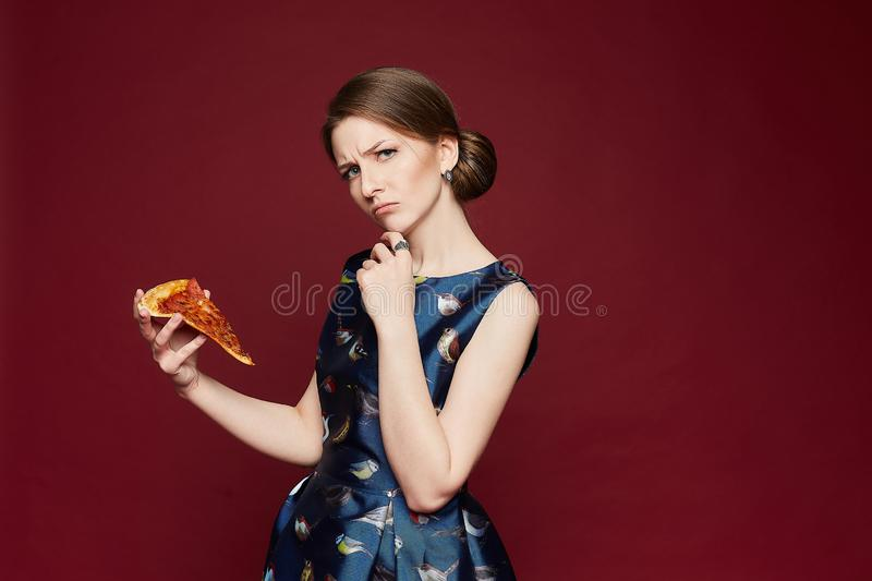 Beautiful brunette model woman with blue eyes in a fashionable blue dress holding a piece of pizza in her hand and. Thinks whether to eat this piece, isolated stock image