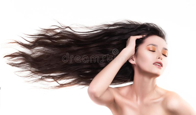 Beautiful brunette naked shoulders girl with flying horizontally. Sideways her long hair touches her face and neck. Nude make-up. Healthy smooth skin. Isolated royalty free stock photo