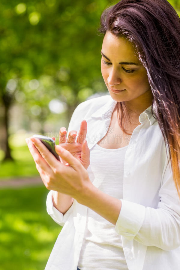 Beautiful brunette in the park sending text. On a sunny day royalty free stock images