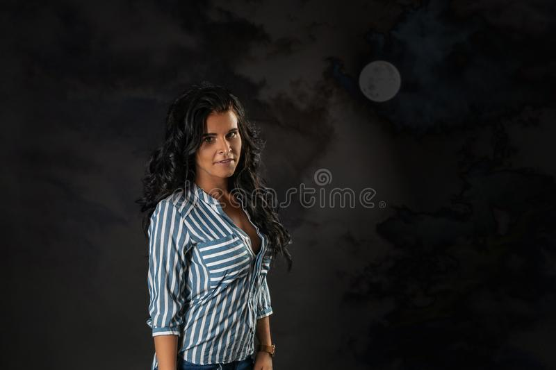 Beautiful brunette with piercing on a background of the night moon sky.  stock photo