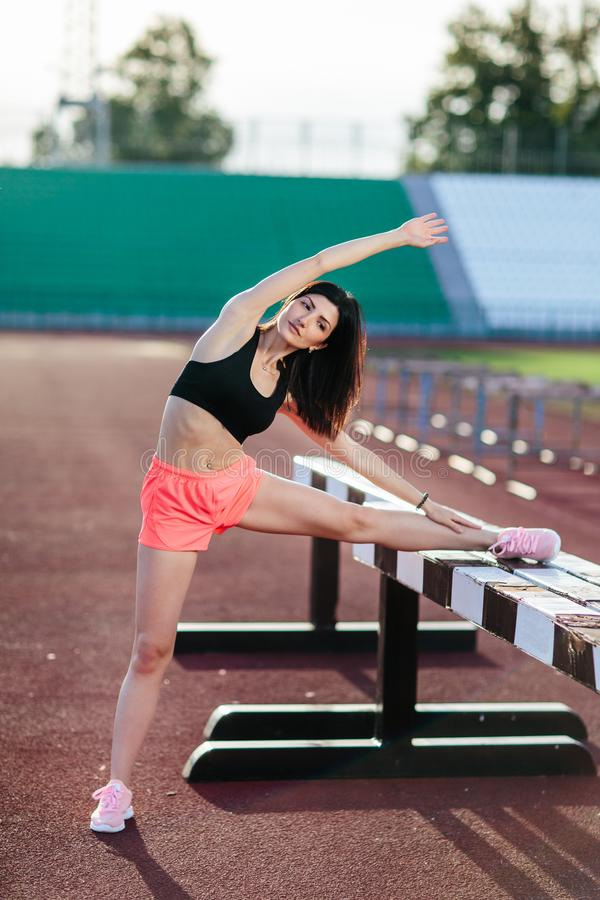 Beautiful brunette runner woman doing stretching leaning her leg on barrier for running stretching before workout - outdoor shot. Sport girl doing exercise in royalty free stock photography