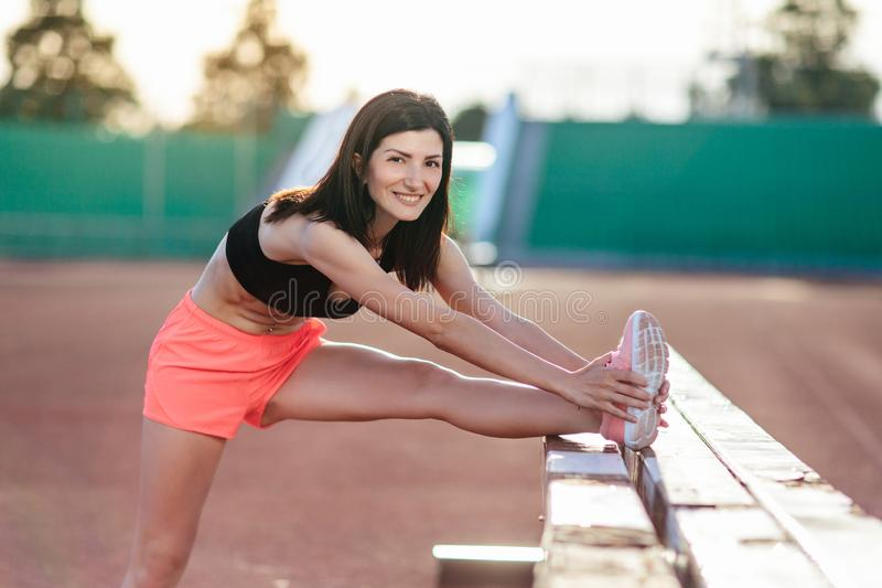 Beautiful brunette runner woman doing stretching leaning her leg on barrier for running stretching before workout - outdoor shot. Sport girl doing exercise in stock photo