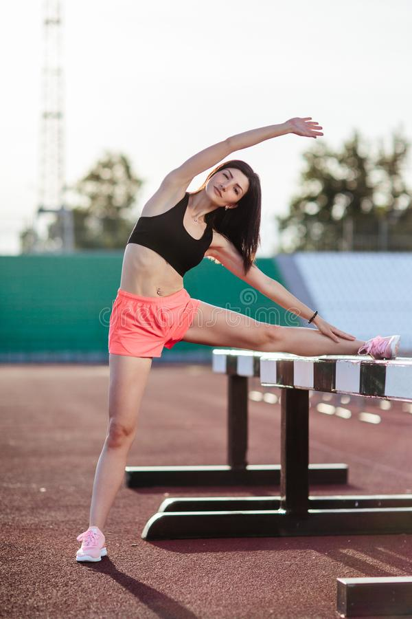 Beautiful brunette runner woman doing stretching leaning her leg on barrier for running stretching before workout - outdoor shot. Sport girl doing exercise in royalty free stock images