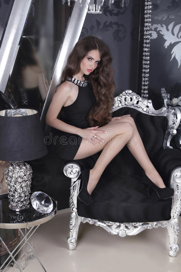 Beautiful brunette sensual girl model in short black dress posing on luxury armchair, at modern apartment stock photos