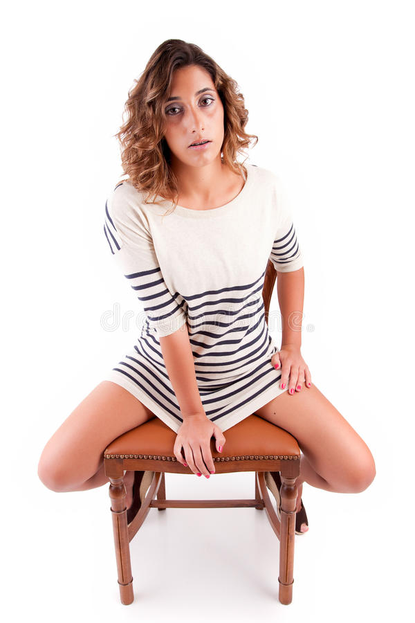 Beautiful brunette sitting on a chair. Isolated royalty free stock images