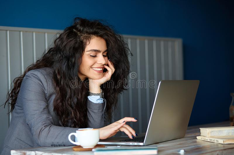 Beautiful brunette sitting in coffee shop and working on computer. Beautiful brunette sitting in coffee shop and working on computer stock images