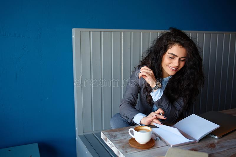 Beautiful brunette sitting in coffee shop and working on computer. Beautiful brunette sitting in coffee shop and working on computer stock photos